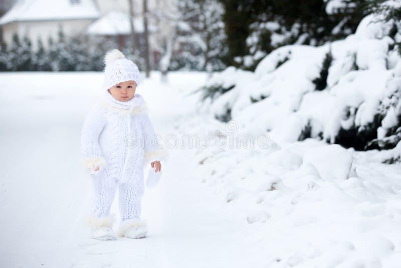 Petit garçon mignon d'enfant en bas âge, jouant dehors avec la neige un jour d'hiver photo libre de droits