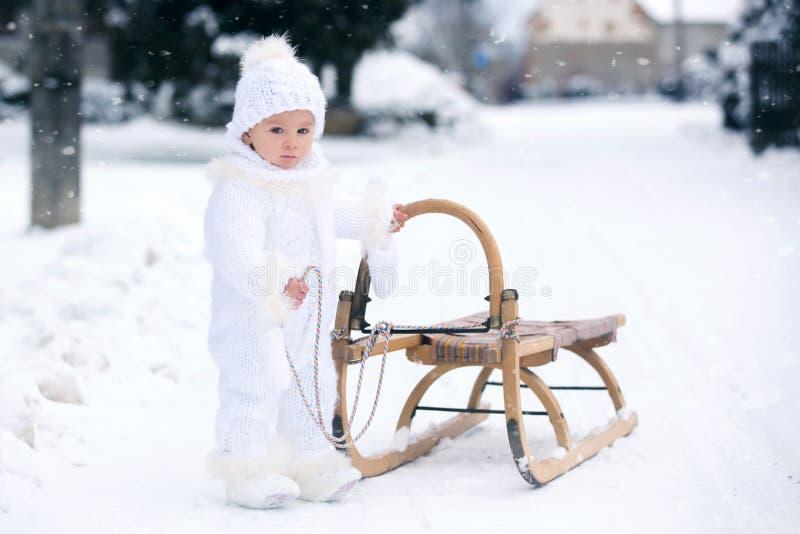 Petit garçon mignon d'enfant en bas âge, jouant dehors avec la neige un jour d'hiver image stock