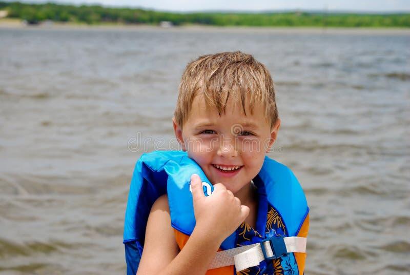 Petit garçon mignon dans le gilet de sauvetage sur le lac photographie stock libre de droits