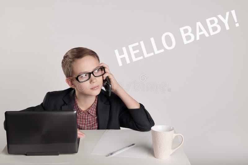 Petit garçon mignon dans un costume parlant au téléphone photographie stock libre de droits