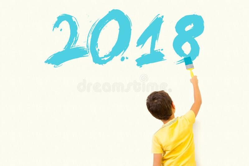Petit garçon mignon dessinant la nouvelle année 2018 avec la brosse de peinture sur wal photographie stock libre de droits