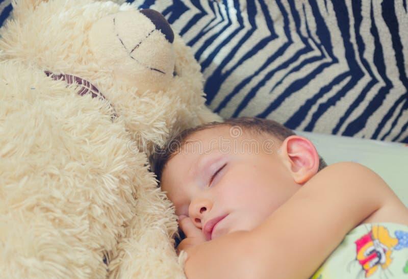 Petit garçon mignon dormant avec son ours de nounours photos libres de droits
