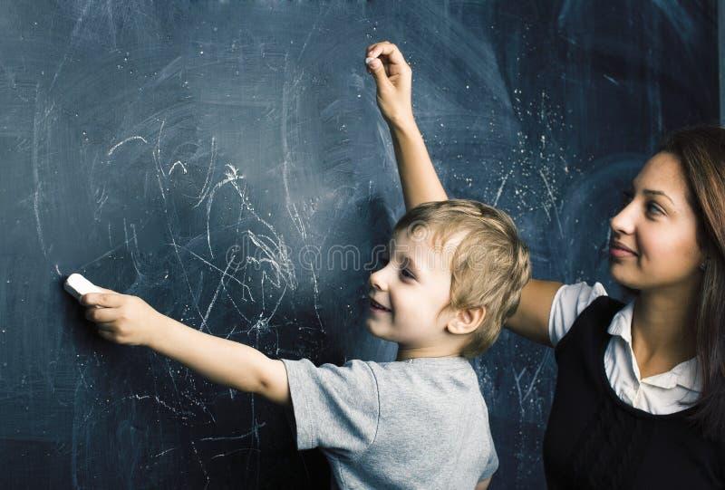 Petit garçon mignon en verres avec le jeune vrai professeur, salle de classe étudiant au kido d'école de tableau noir photos libres de droits