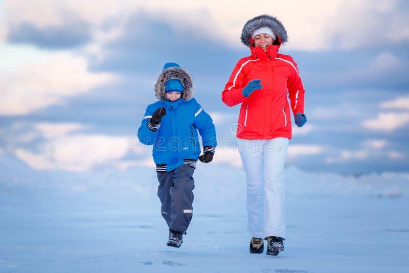 Petit garçon mignon et sa mère sur la plage glaciale images libres de droits