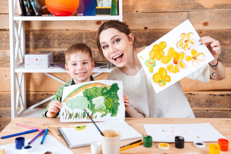 Petit garçon mignon heureux et sa mère montrant leurs peintures images libres de droits
