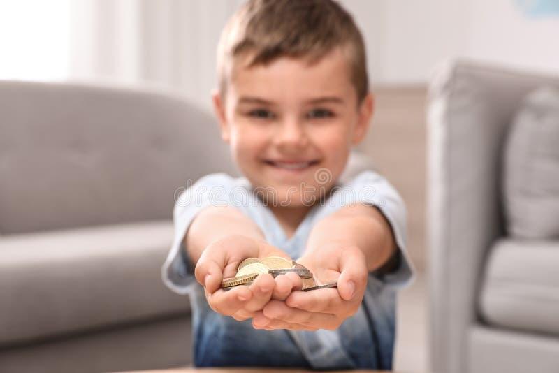 Petit garçon mignon heureux tenant des pièces de monnaie à la maison image libre de droits