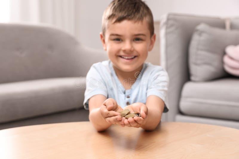 Petit garçon mignon heureux tenant des pièces de monnaie à la maison images stock