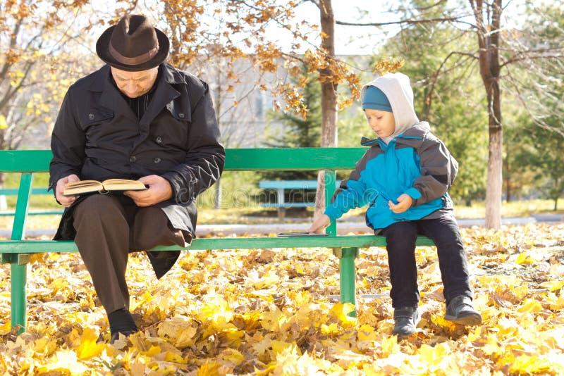 Petit garçon mignon jouant à côté de son grand-père images stock