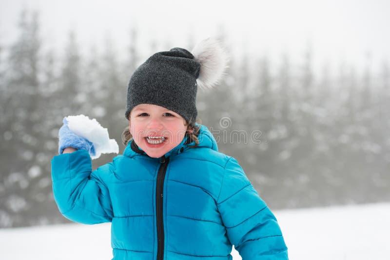 Petit garçon mignon jouant dehors en nature d'hiver image stock