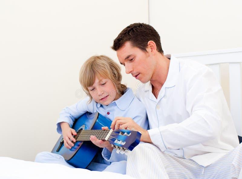 Petit garçon mignon jouant la guitare avec son père photographie stock