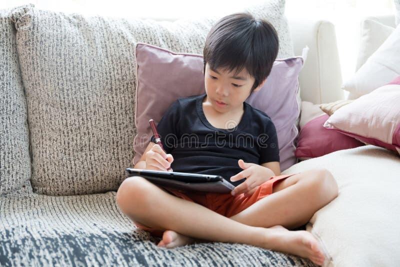 Petit garçon mignon jouant le PC de comprimé images libres de droits