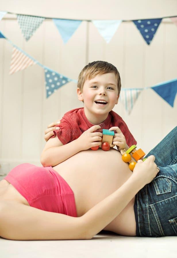 Petit garçon mignon jouant sur le ventre de la mère image stock