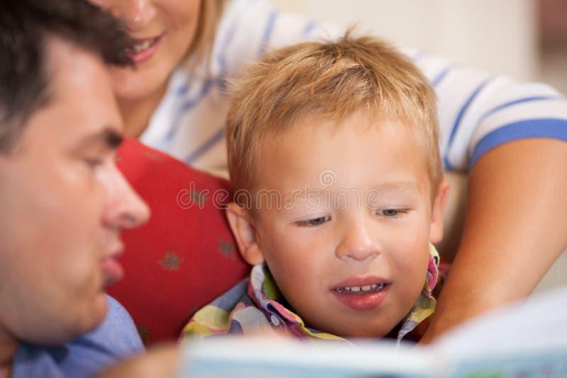 Petit garçon mignon lisant un livre avec ses parents photos libres de droits