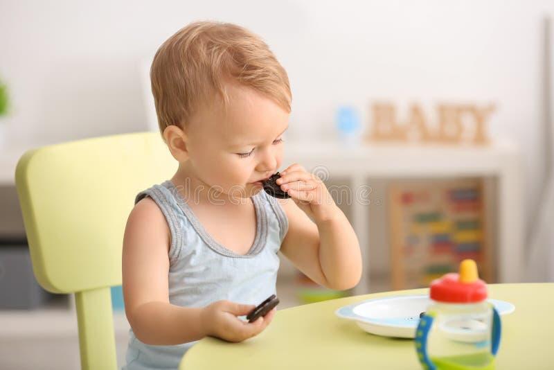 Petit garçon mignon mangeant des biscuits à la table à l'intérieur photographie stock libre de droits