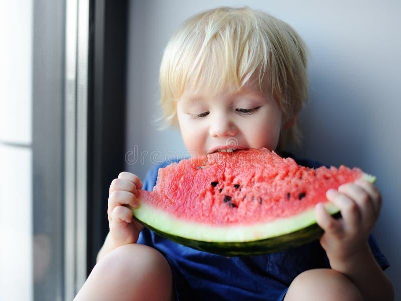 Petit garçon mignon mangeant la pastèque se reposant sur le rebord de fenêtre photo libre de droits