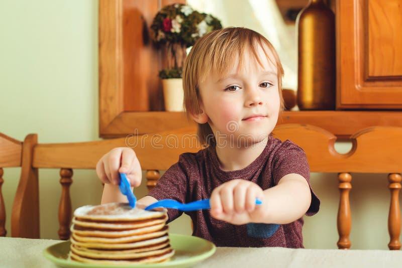 Petit garçon mignon mangeant une pile de crêpes dans la cuisine images stock