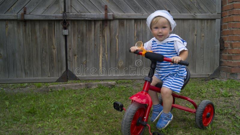 Petit garçon mignon montant un vélo rouge dans la cour photo libre de droits