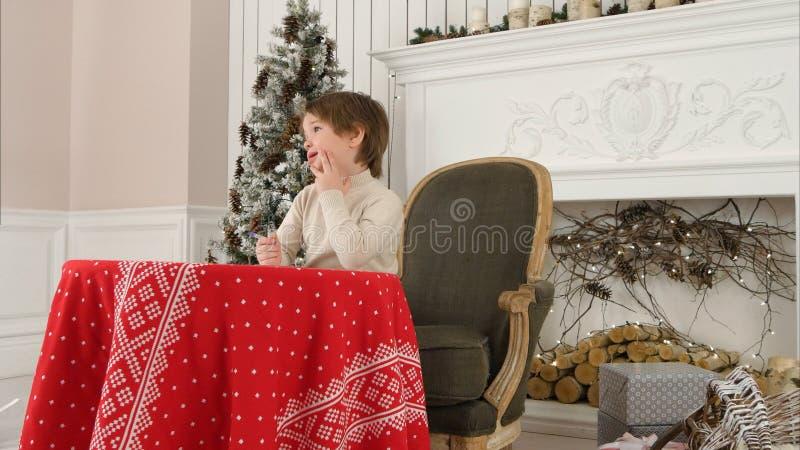 Petit garçon mignon pensant quoi écrire dans sa lettre à Santa Claus image libre de droits
