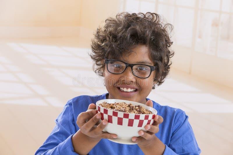 Petit garçon mignon prenant le petit déjeuner à la maison buvant un grand bol de lait dans le T-shirt bleu images stock