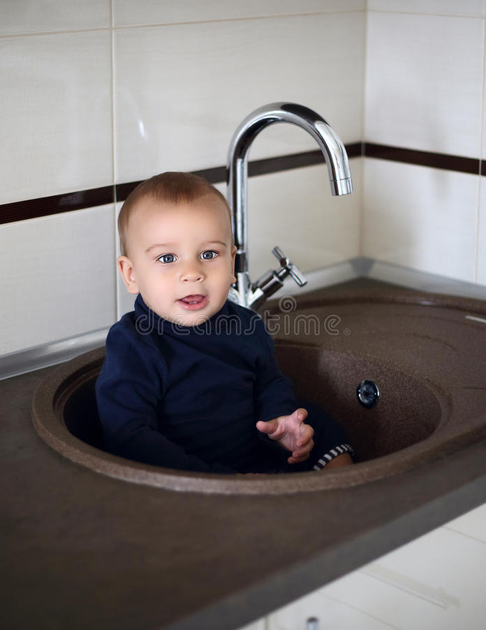 Petit garçon mignon s'asseyant dans le bassin photos stock