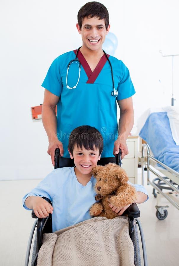 Petit garçon mignon s'asseyant sur le fauteuil roulant et un docteur image stock