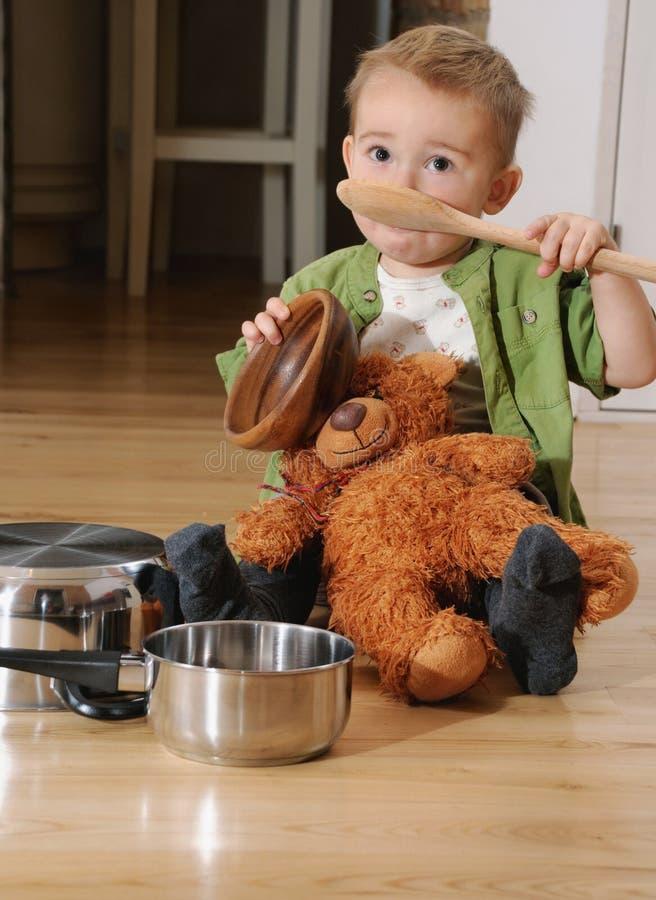 Petit garçon mignon s'asseyant sur le plancher de cuisine jouant avec des pots photographie stock