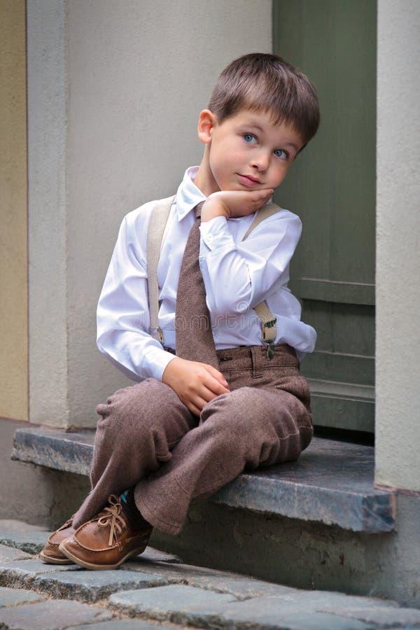 Petit garçon mignon s'asseyant sur le porche à l'extérieur dans la ville photographie stock libre de droits