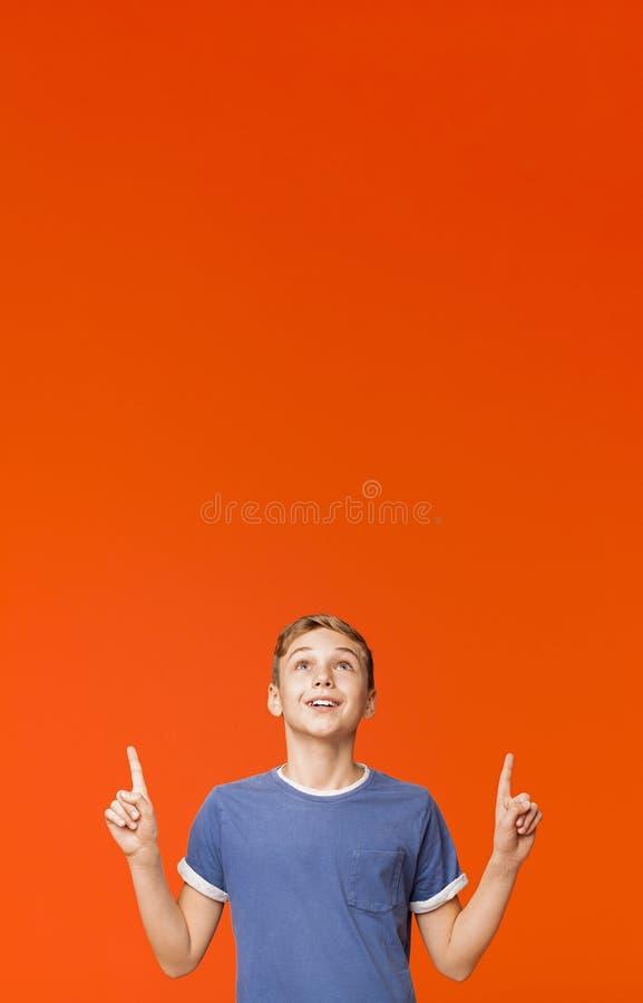 Petit garçon mignon se dirigeant sur le fond orange photographie stock libre de droits