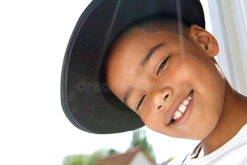 Petit garçon mignon souriant avec le chapeau noir image stock