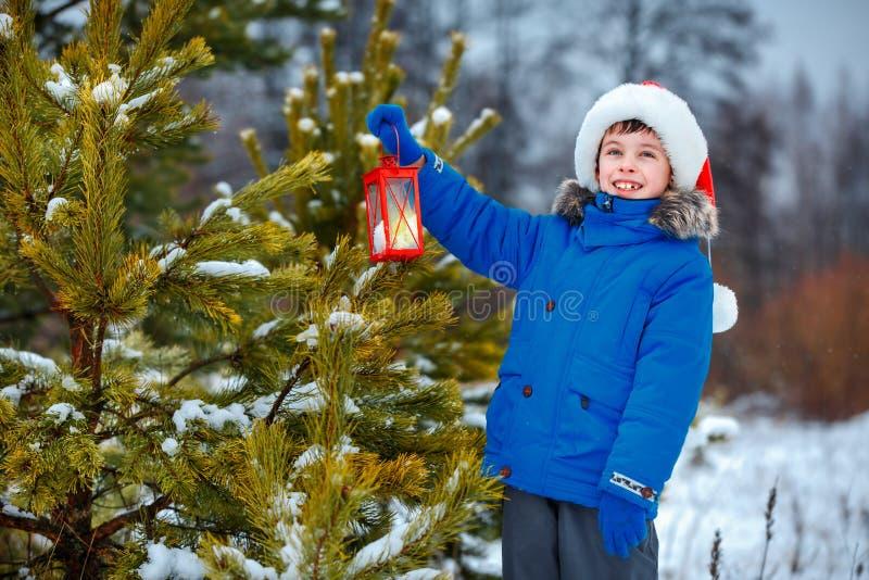 Petit garçon mignon tenant la lanterne de Noël dehors le jour de neige d'hiver image libre de droits