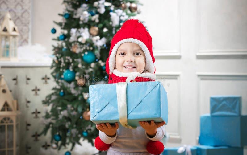 Petit garçon mignon tenant un cadeau contre l'arbre de Noël photo libre de droits