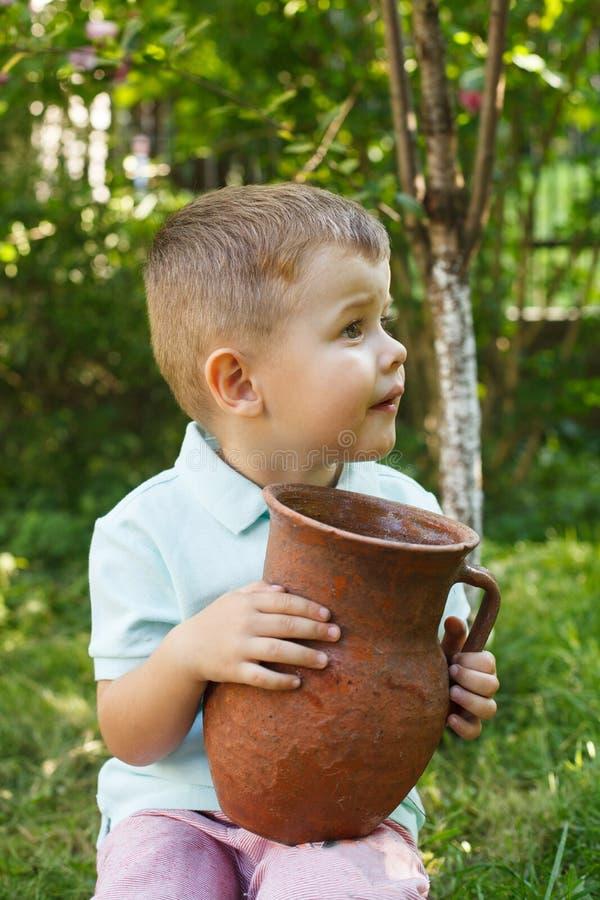 Petit garçon mignon tenant un vieux pot d'argile Cruche de lait image libre de droits