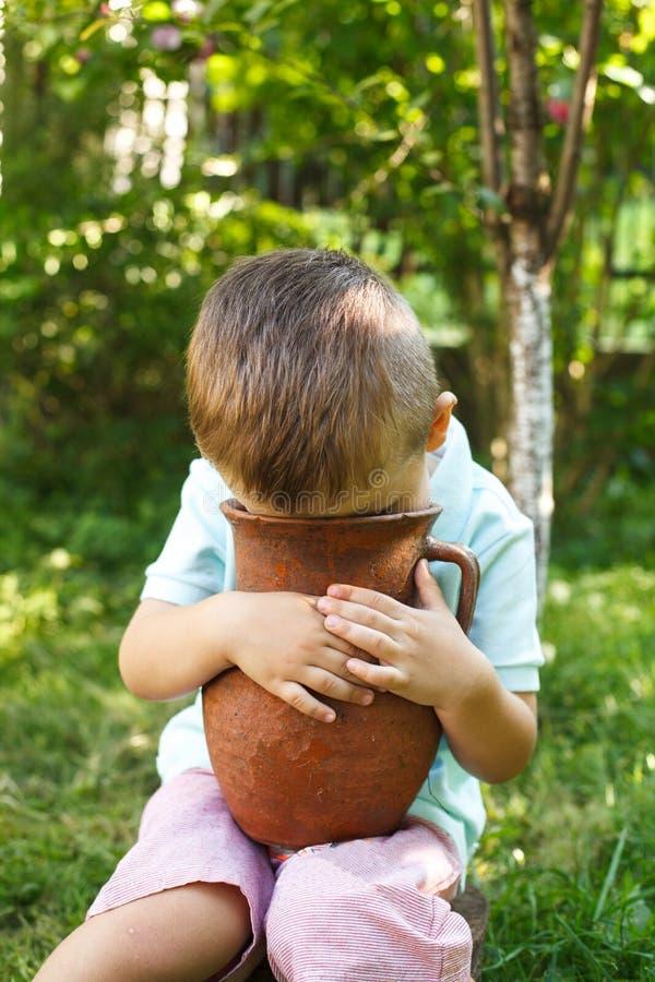 Petit garçon mignon tenant un vieux pot d'argile Cruche de lait images libres de droits
