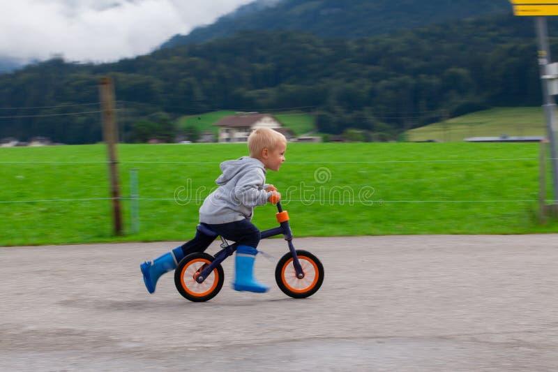 Petit garçon montant un vélo sur l'eau photographie stock libre de droits