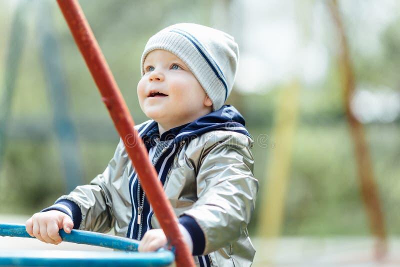 Petit garçon montant une oscillation dans le terrain de jeu de parc photos libres de droits