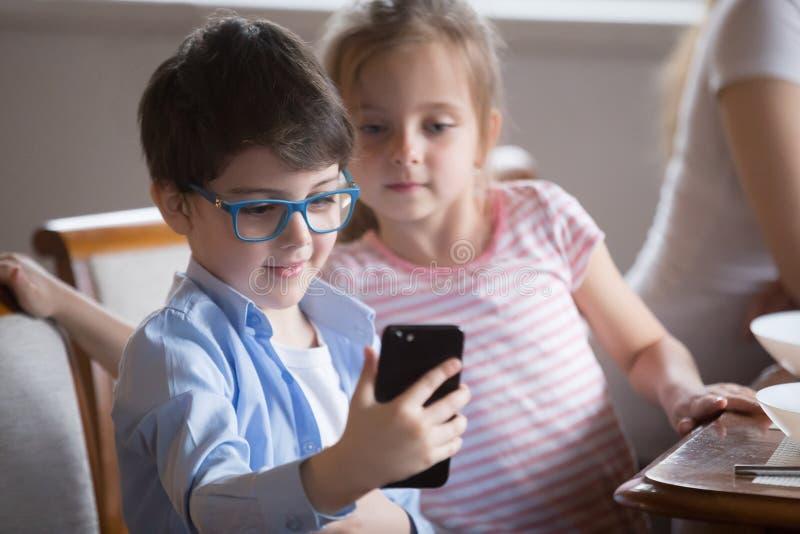 Petit garçon montrant la vidéo sur le smartphone à la soeur photos libres de droits