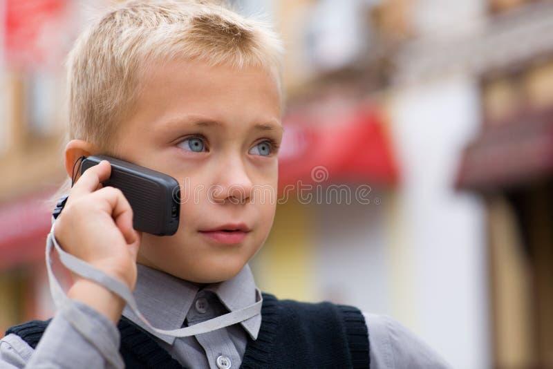 Petit garçon parlant sur un téléphone portable photo stock
