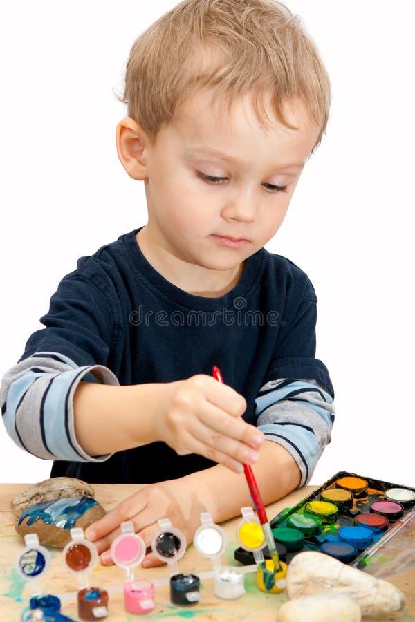Petit garçon peignant les pierres avec l'aquarelle images stock
