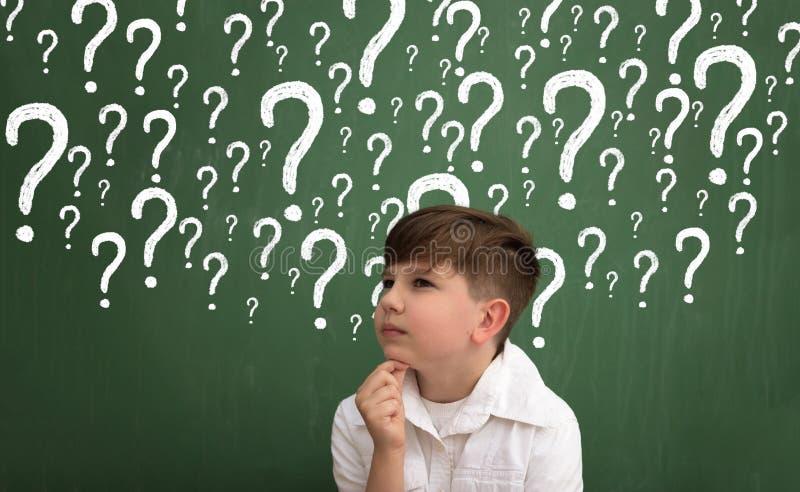 Petit garçon pensant les points d'interrogation entourés photo stock
