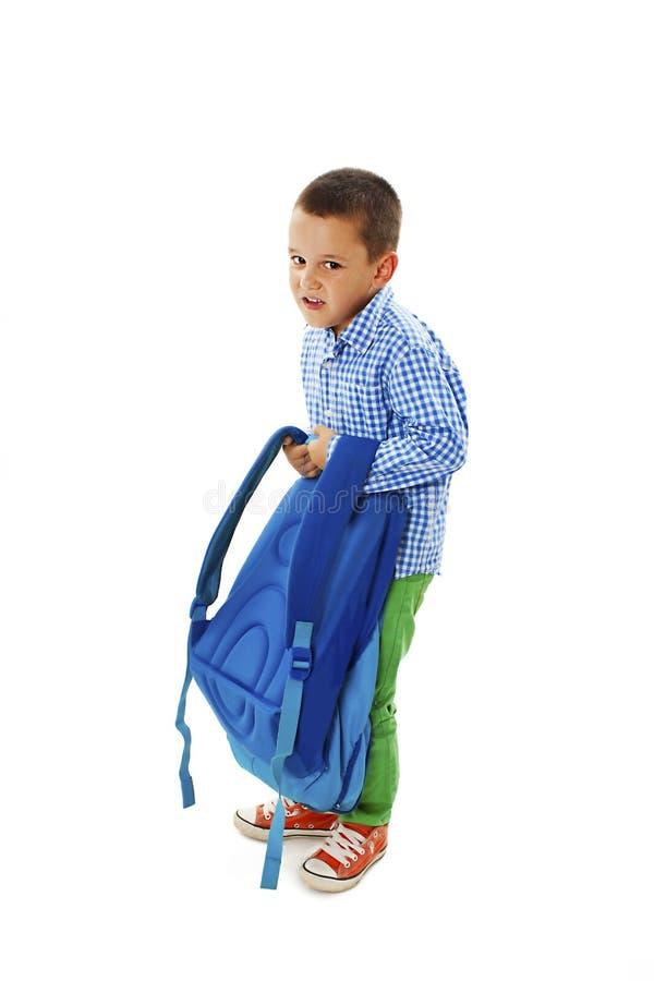 Petit garçon portant le sac d'école lourd images libres de droits