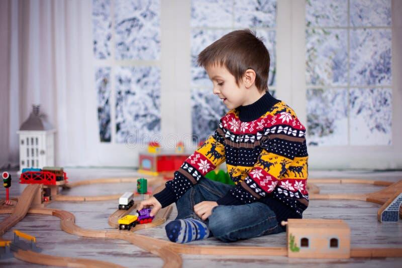 Petit garçon préscolaire adorable, jouant avec les trains et le Ra en bois photo libre de droits