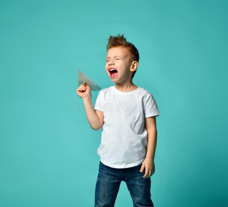 Petit garçon prêt à lancer un avion et un cri de papier avec les yeux fermés Opération neuve images libres de droits