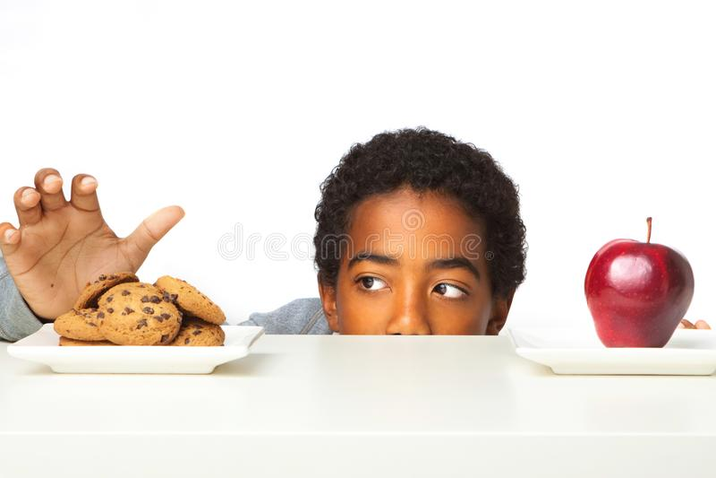 Petit garçon prenant des décisions des vers sains de consommation malsaines images libres de droits