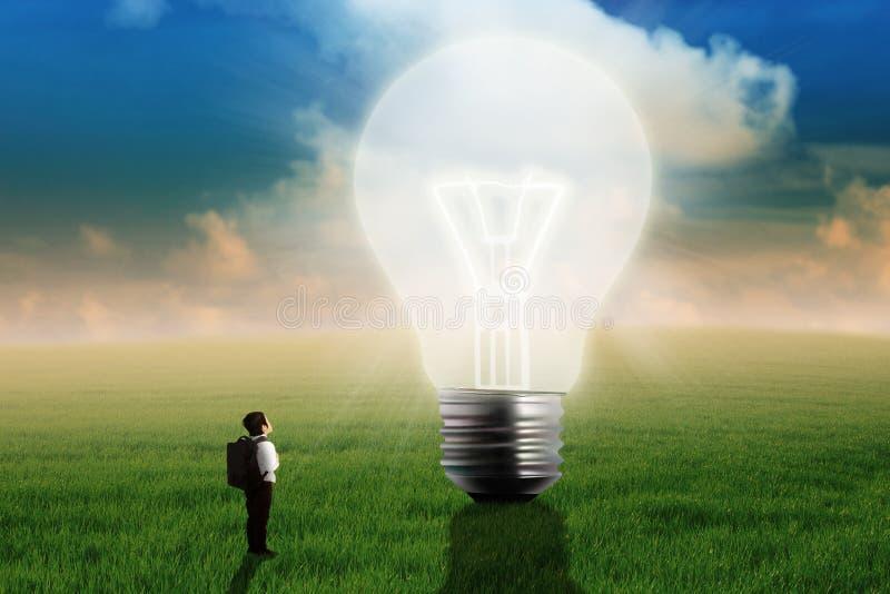 Petit garçon regardant la grande ampoule image libre de droits