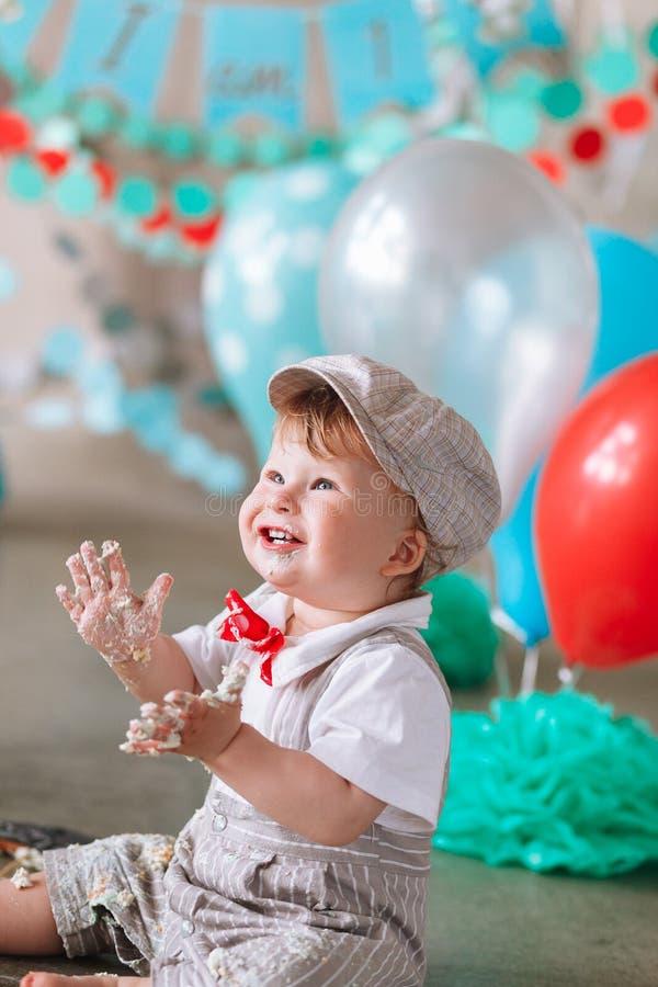 Petit garçon regardant le côté avec la bouche couverte en glaçage et gâteau blancs en contexte décoré de studio Cakesmash d'anniv photos libres de droits