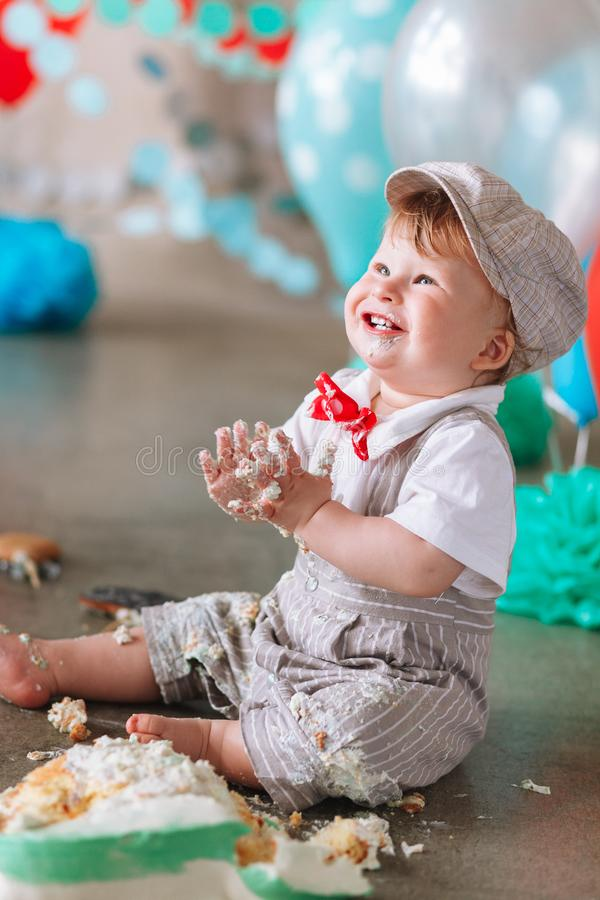Petit garçon regardant le côté avec la bouche couverte en glaçage et gâteau blancs en contexte décoré de studio Cakesmash d'anniv photos stock