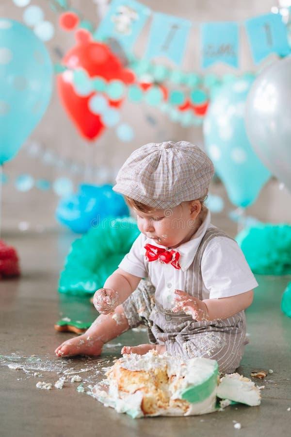 Petit garçon regardant le côté avec la bouche couverte en glaçage et gâteau blancs en contexte décoré de studio Cakesmash d'anniv image stock