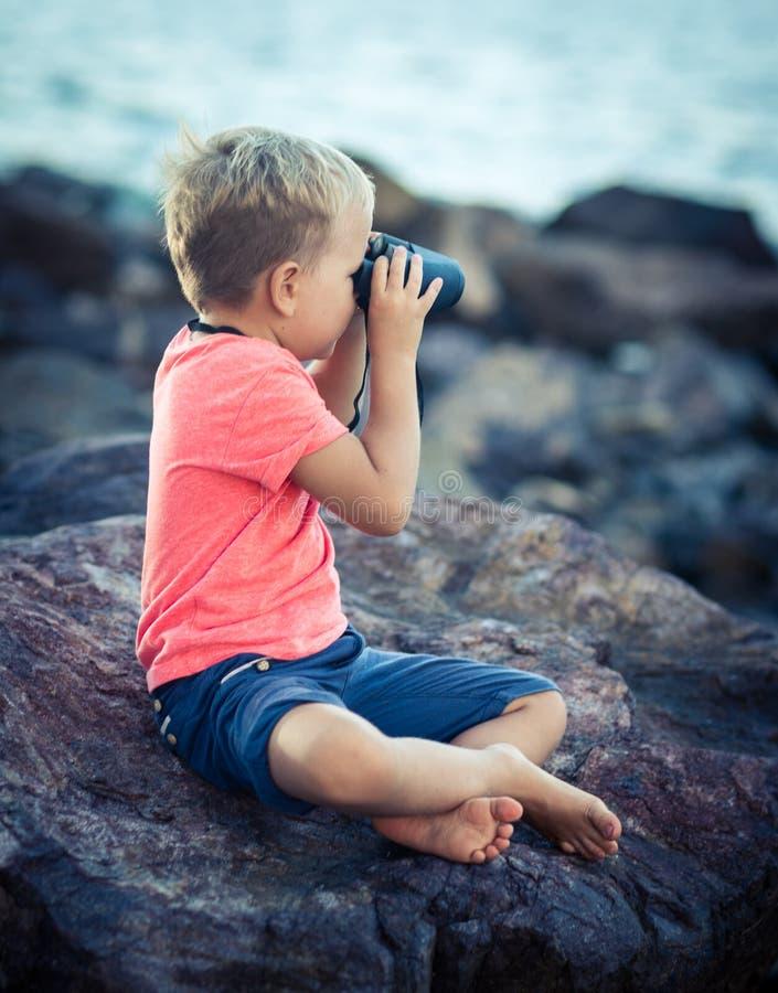 Petit garçon regardant loin avec des jumelles photographie stock libre de droits