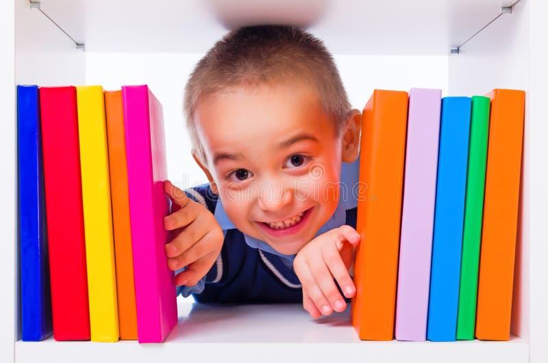 Petit garçon regardant par des étagères à livres photo stock