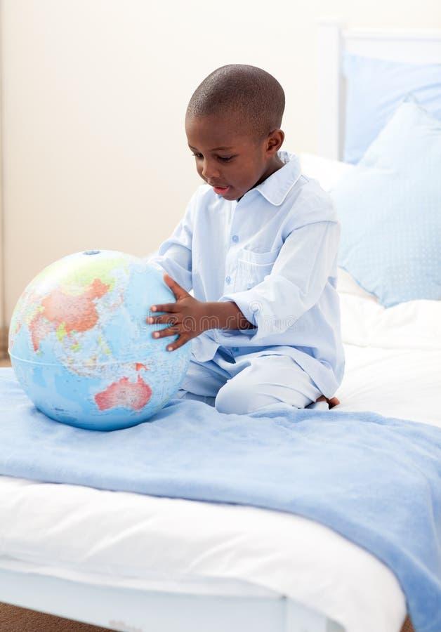 Petit garçon retenant un globe terrestre image stock